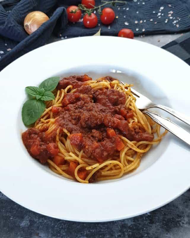 In einem weißen Pasta Teller angerichtet, Spaghetti mit Bolognese Soße, dekoriert mit einem Basilikum Blatt. Am Tellerrand liegen eine Gabel und ein Löffel.