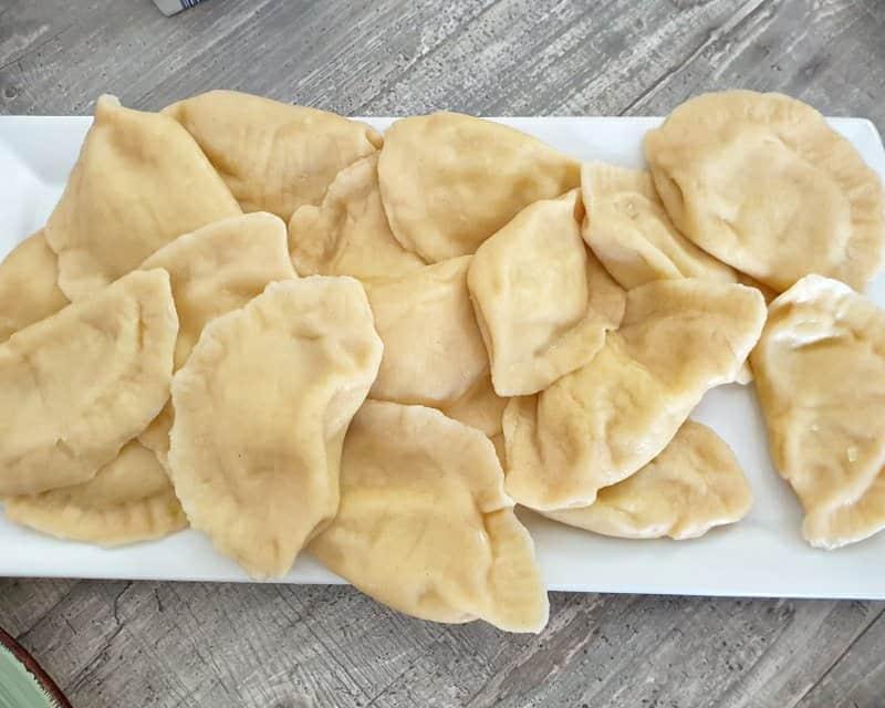 Auf einer weißen Servierplatte die fertig gekochten Wareniki.