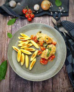 Auf einem grünen Teller sieht man angebratene Schupfnudeln mit Hähnchenbrust in cremiger Frischkäse-Parmesan-Soße.