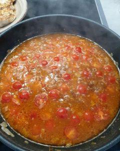 Die Mischung für die cremige Frischkäse-Parmesan-Soße wird mit Rinderbrühe abgelöscht.