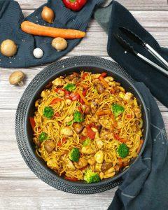 In einer Pfanne angerichtet Asia Nudelpfanne mit Gemüse und Hähnchen. Im Hintergrund auf einem Küchenhandtuch eine Möhre, ein paar Pilze und eine rote Paprika. Neben der Pfanne liegt eine Zange.