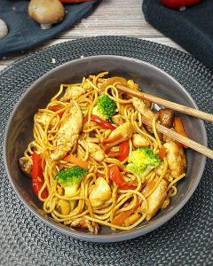 In einer grauen Schale angerichtet Asia Nudelpfanne mit Gemüse und Hähnchen. Im Hintergrund auf einem Küchenhandtuch eine Möhre, ein paar Pilze und eine rote Paprika. In der Schale sind zwei Essstäbchen.