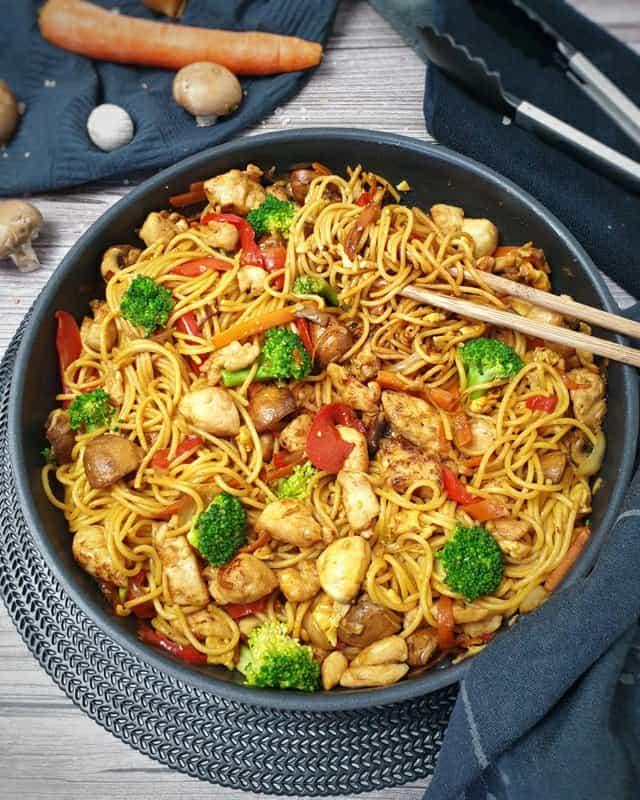 In einer Pfanne angerichtet Asia Nudelpfanne mit Gemüse und Hähnchen. Im Hintergrund auf einem Küchenhandtuch eine Möhre, ein paar Pilze und eine rote Paprika. Neben der Pfanne liegt eine Zange. In der Pfanne stecken zwei Essstäbchen.