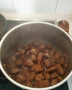 Nachdem die Zwiebeln und der Knoblauch dazu gekommen sind wird das Gulaschfleisch mit Rotwein abgelöscht.