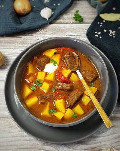 Gulaschsuppe in einer grauen Schale angerichtet und fotografiert. In der Schale steckt ein Löffel mit Holzgriff, daneben liegt ein Küchenhadtuch, darauf zu sehen eine Kartoffel, eine Zwiebel, eine Knoblauchzehe und ein Lorbeerblatt.