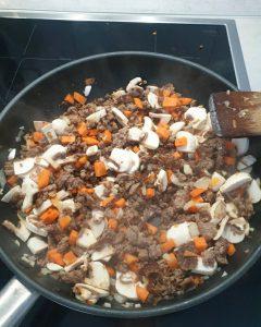 In einer Pfanne angebratenes Hackfleisch mit Möhren und Champignons.