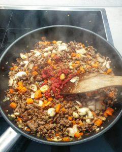 In einer Pfanne Hackfleisch mit Tomatenmark, Möhren und Sellerie.