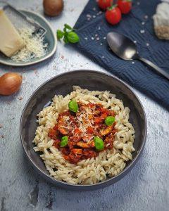 In einer grauen, runden Schale angerichtet Bolognese mit Pilzen und Fusilli. Garniert mit ein paar Basilikum Blättern und etwas geriebenen Parmesan.