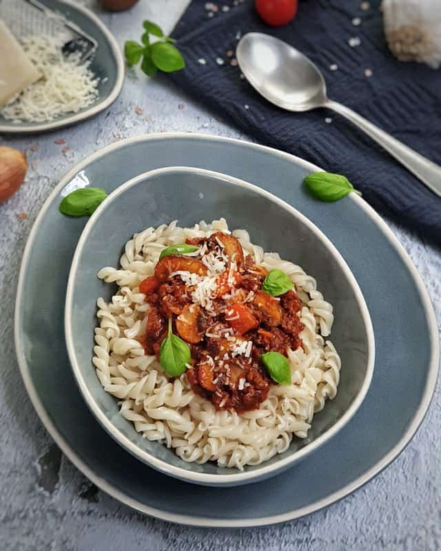 In einer graublauen ovalen Schale angerichtet Bolognese mit Pilzen und Fusilli. Garniert mit ein paar Basilikum Blättern und etwas geriebenen Parmesan.