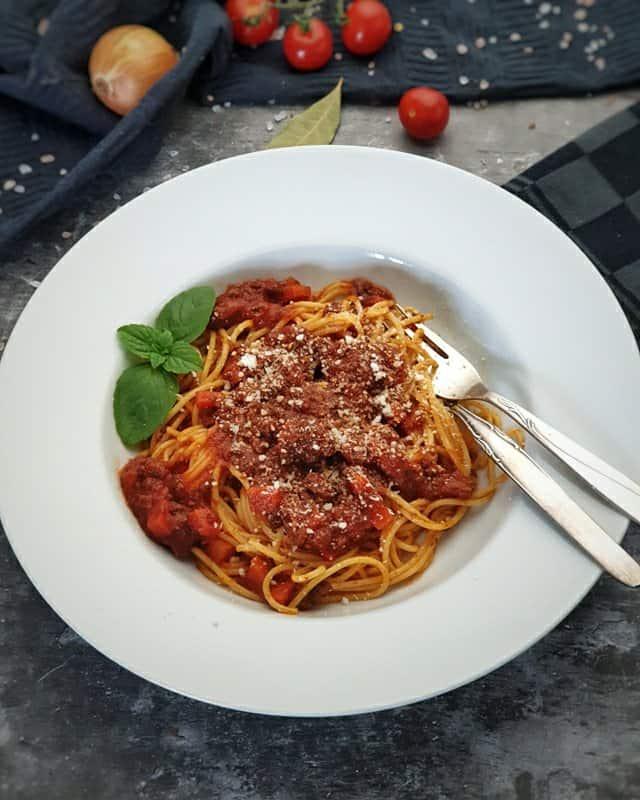 In einem weißen Pasta Teller angerichtet Spaghetti Bolognese mit Parmesan bestreut und einem Baslilikumblatt dekoriert.