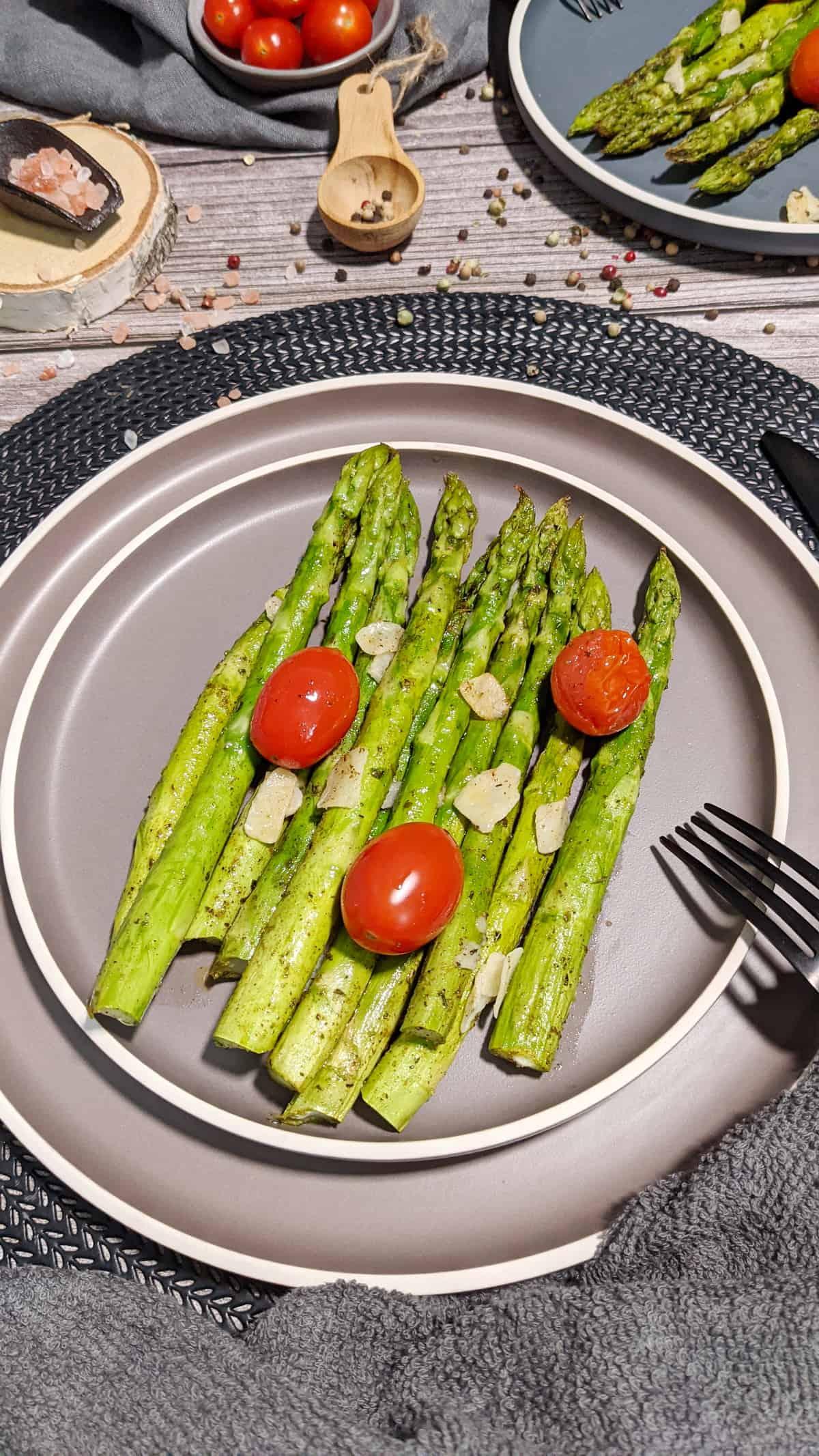 Auf einem grauen Teller angerichtet gebackener Spargel mit Tomaten und Parmesan. Im Hintergrund Deko.