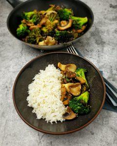In einer braunen Schale angerichtet eine Portion Basmatireis mit Asia Gemüse Pfanne. Im Hintergrund steht eine Pfanne mit den Gemüse, neben der Schale liegt Besteck.