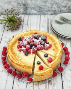 Ein Käsekuchen mit frischen Beeren auf einem Kuchengitter. Die Beeren sind mit Puderzucker und weißen Schokoladen Raspeln dekoriert.