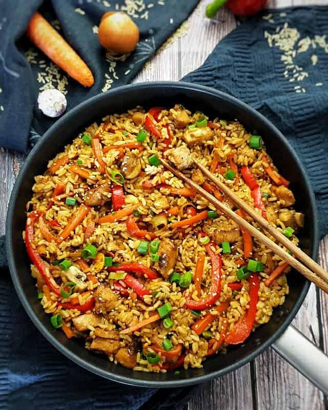 Gebratener Asia Reis mit Gemüse und Hähnchen in einer Pfanne serviert. Mit Sesam und ein paar Frühlingszwiebeln dekorativ bestreut.