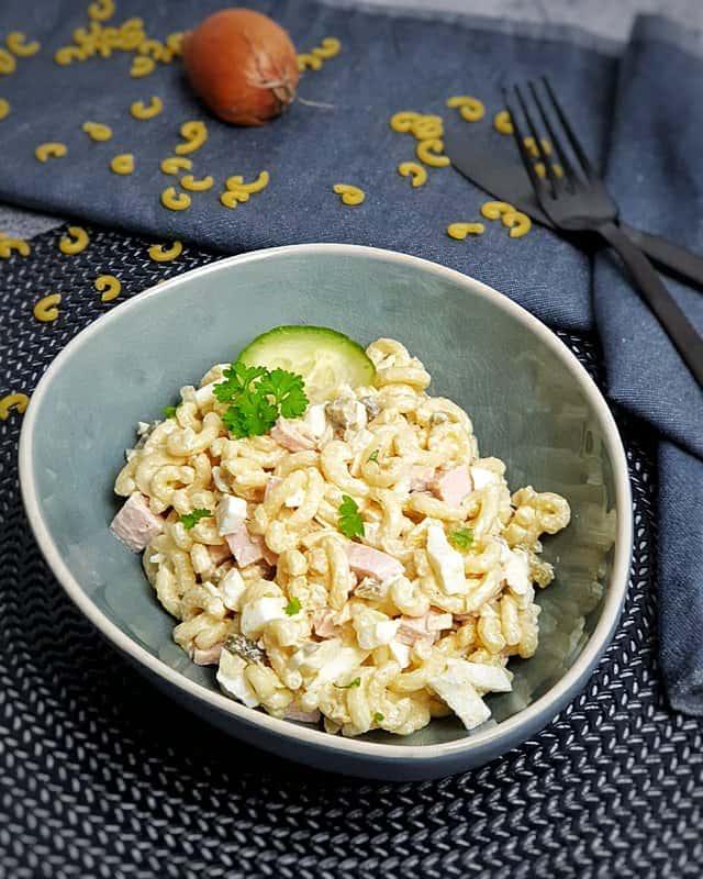 In einer blauen ovalen Schale angerichtet Nudelsalat mit Mayonnaise, Fleischwurst, Gewürzgurken und Eiern. Mit frischer Petersilie bestreut. In der Mitte der Schale eine Gurkenscheibe.