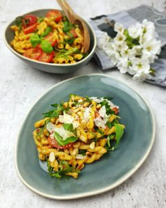 Auf einem blauen ovalen Teller angerichtet ein italienischer Nudelsalat mit Rucola, Tomaten und Parmesan.