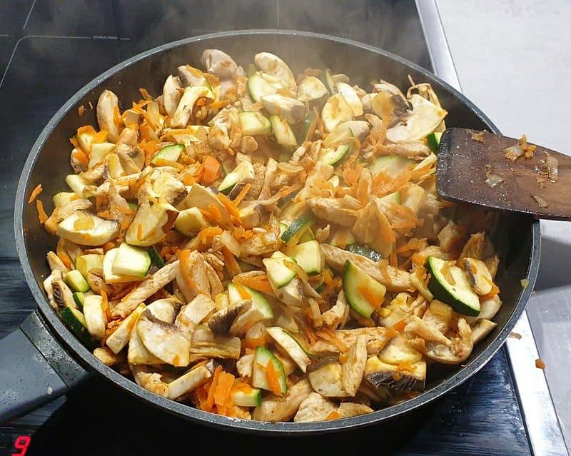 Gebratenes, gewürztes Gemüse mit Hähnchen in einer Pfanne.