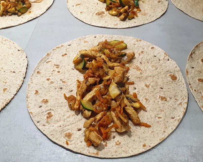 Wraps mit Gemüse Hähnchen Füllung auf einer Küchenplatte.