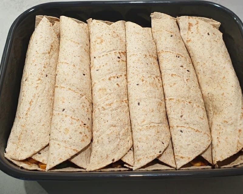 6 gefüllte und gerollte Wraps in einer Auflaufform nebeneinander.