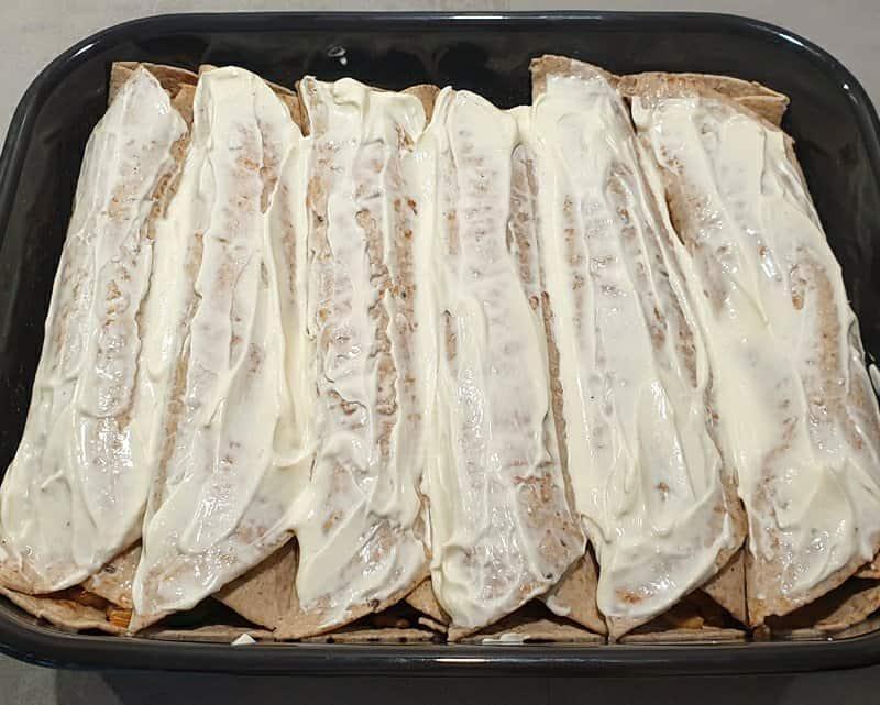 Gefüllten Wraps mit einer Creme Fraiche bestrichen in einer Auflaufform.