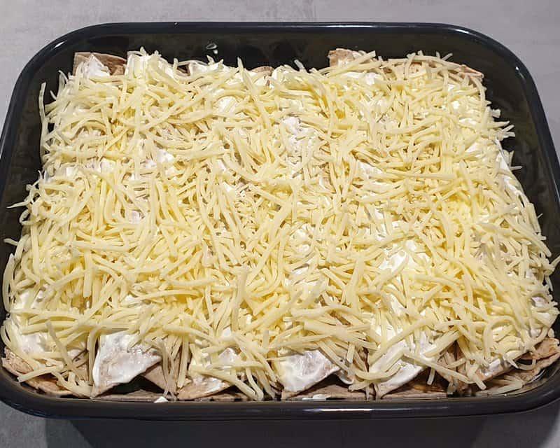 In einer Auflaufform gefüllte Wraps mit Käse bestreut.