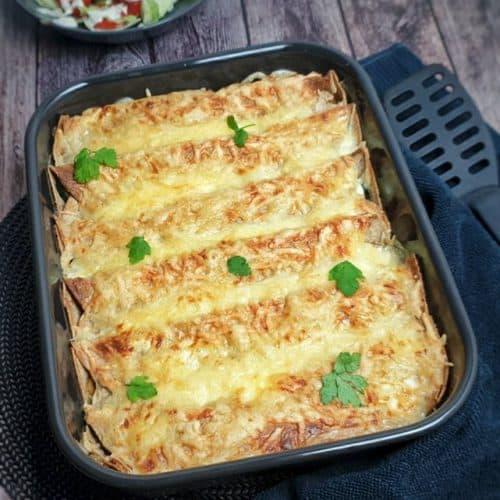 Überbackene Wraps aus dem Ofen mit Käse überbacken und mit Petersilie bestreut in einer dunkelgrauen Auflaufform fotografiert.