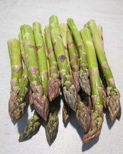 Grüner geschälter Spargel gewaschen und geschält auf einer Küchen Arbeitsplatte.