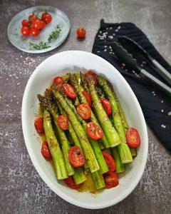 In einer weißen Auflaufform fotografiert Grüner Spargel aus dem Ofen mit Tomaten.