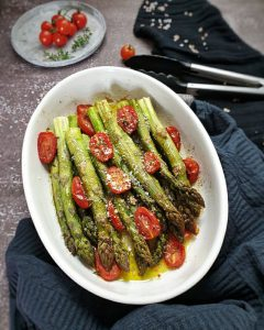 In einer weißen Auflaufform fotografiert Grüner Spargel aus dem Ofen mit Parmesan und Tomaten.