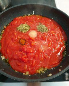 In einer Pfanne eine Tomatensoße mit Gewürzen.