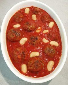 In einer Auflaufform angebratene Hackbällchen in Tomatensoße mit ein paar weißen Bohnen.