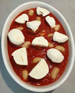 In einer Auflaufform Hackbällchen in Tomatensoße mit Mozzarella in Scheiben belegt.