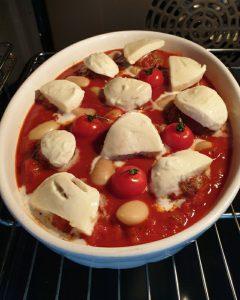 Im Backofen eine weiße Auflaufform mit Hackbällchen in Tomatensoße und mit Mozzarella belegt.