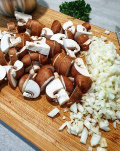 Klein geschnittene Zwiebeln und Champignons auf einem Schneidebrett.