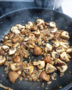 Champignons und Zwiebelwürfel angebraten in einer Pfanne eingekocht mit Weißwein.