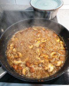 Champignons und Zwiebelwürfel angebraten in einer Pfanne mit Brühe abgelöscht.