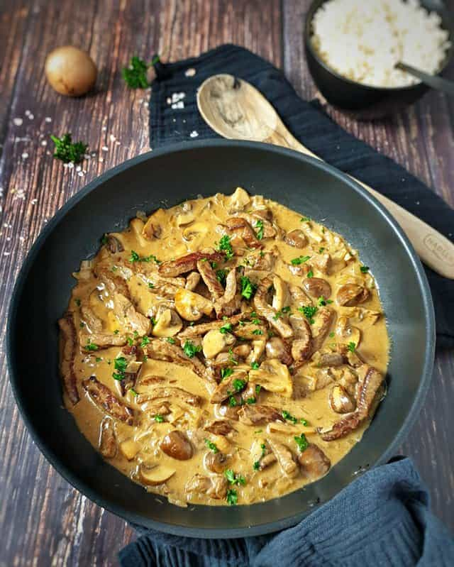 Züricher Geschnetzeltes in einer Pfanne serviert mit Petersilie bestreut. Im Hintergrund eine Schale Reis. Neben der Pfanne ein Holzlöffel.