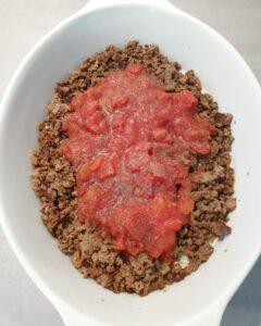 Hackfleisch und gehackte Tomaten in einer Auflaufform.