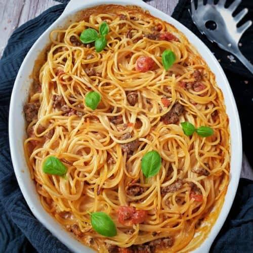 Spaghetti Auflauf mit Hackfleisch in einer weißen Auflaufform mit Basilikum Blätter bestreut. Um die Auflaufform ein dunkles Küchenhandtuch. Daneben auf einem weiteren Küchentuch eine Spaghetti Zange.