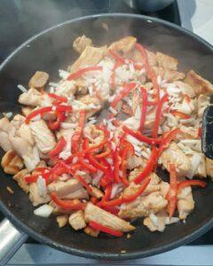 In einer Pfanne angebratenes Hähnchen Fleisch mit Paprika und Zwiebeln.
