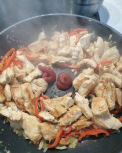 In einer Pfanne angebratenes Fleisch mit Paprika und Tomatenmark.