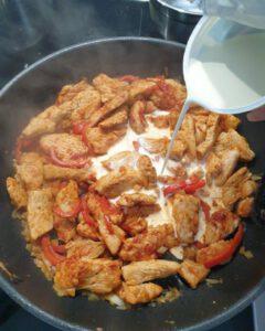 Fleisch und Paprika in einer Pfanne mit Sahne abgelöscht.