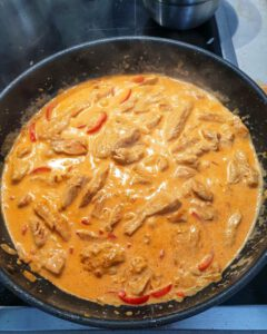 In einer Pfanne Paprika Rahm Soße mit Hähnchen.