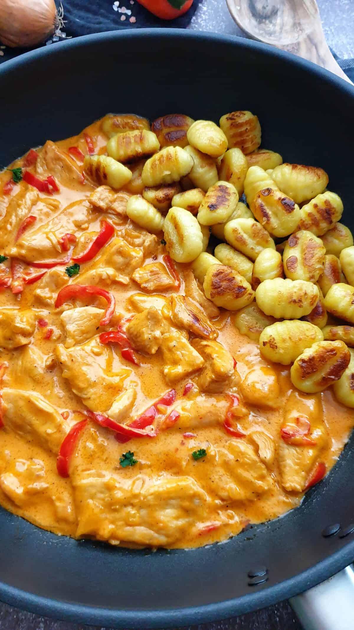 Gnocchi neben Paprika-Rahm-Geschnetzeltes in einer Pfanne angerichtet,