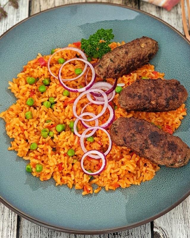 Auf einem blauen Teller angerichtet Cevapcici mit Djuvec Reis und roten Zwiebel Ringen.