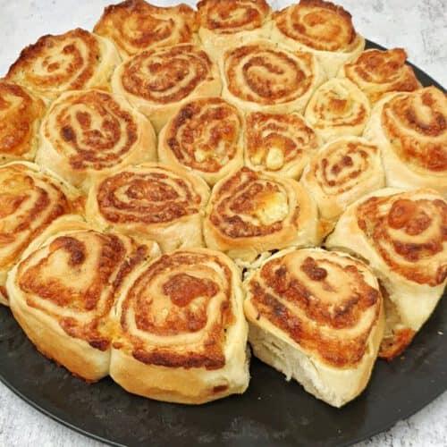 Zupfbrot mit Frischkäse Rosenbrot auf einem dunklen runden großen Teller angerichtet.