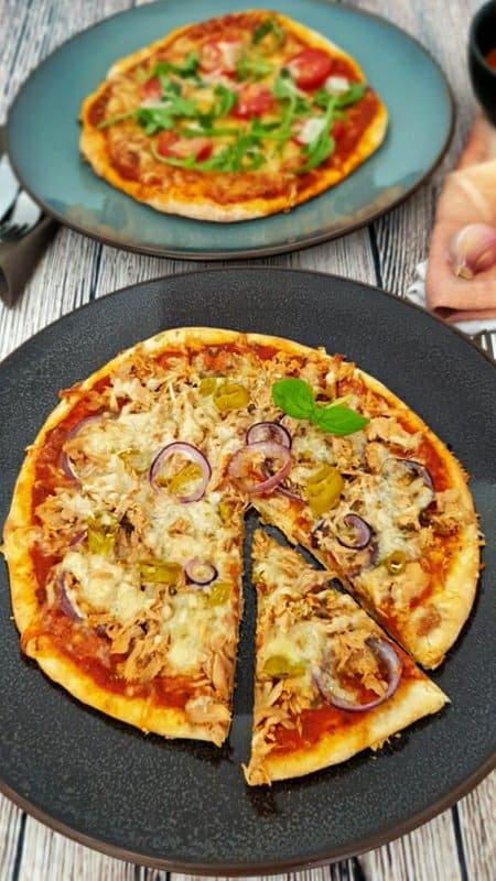 Auf einem dunklen großen Teller eine Dinkel Pizza mit Thunfisch, Zwiebeln und Käse zum Rezept für Grundrezept für Dinkel Pizzateig.