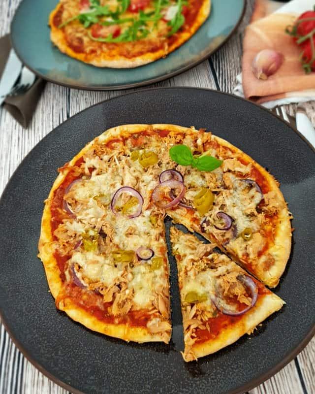 Auf einem dunklen großen Teller eine Dinkel Pizza mit Thunfisch, Zwiebeln und Käse.