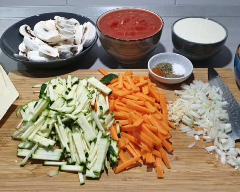 Geschnittenes Gemüse für Gemüse Lasagne auf einem Holz Schneidebrett