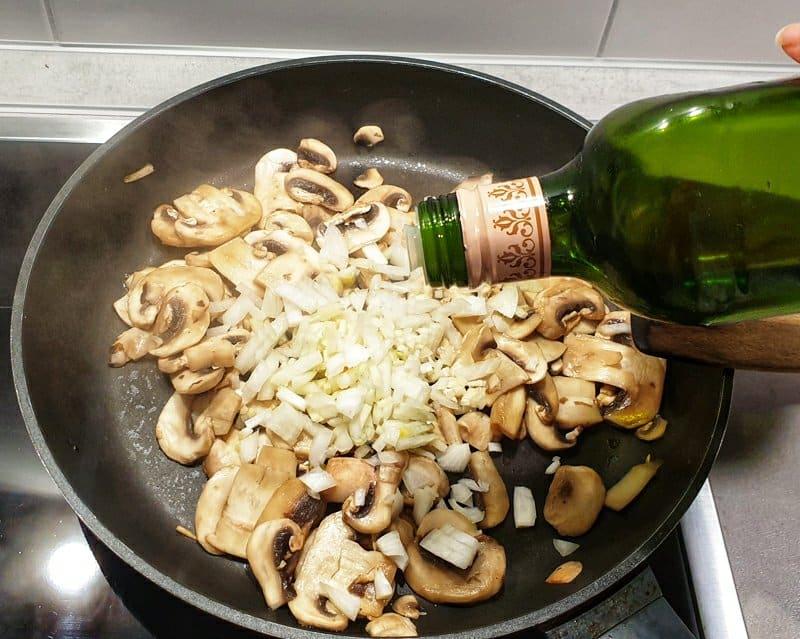 Angebratene Champignons mit Zwiebel Würfel und Öl in einer Pfanne.
